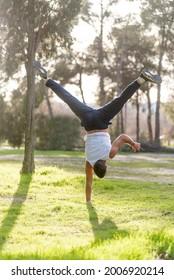Gymnastic man handstand on one hand doing acrobatic posture