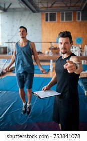 gymnastics athlete exercising with coach; young guy has workout with personal trainer;