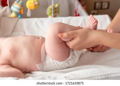 Gymnastikbaby. Frauen machen Übungen mit Kind für seine Entwicklung. Massage ein kleines Neugeborenes Baby, Übungen auf den Beinen. Babymassage, Massage der Mutter Hand ihres Babys.