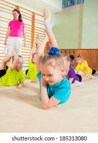 Gymnastics coach teaching little girls