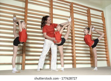 Gymnastics coch teaching little girls