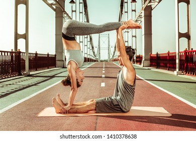 Gymnastics for two people. Smiling young man and woman doing an acroyoga jedi box pose on a bridge over the river