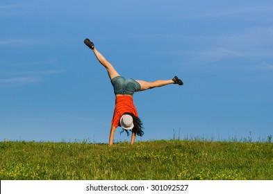 gymnastics woman doing cartwheel on nature backgrounds. motion blur effect