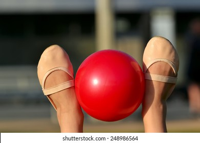 Gymnast's feet in toe shoes with red ball