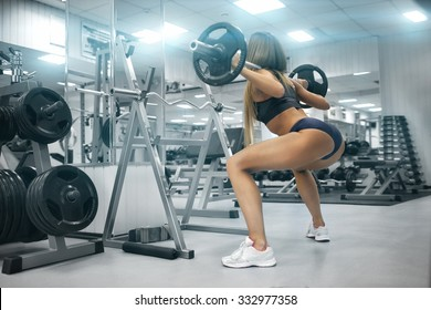 Gym.Sporty girl posing with barbell