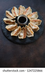 Gyoza dumplings with dipping sauce served on a stone slate tray, vertical shot with copyspace on a brown metal background