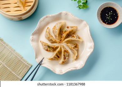Gyoza dumplings with duck cooked in bamboo steamer served on a plate with soy sauce, sesame seeds and cilantro. Top view, blue background