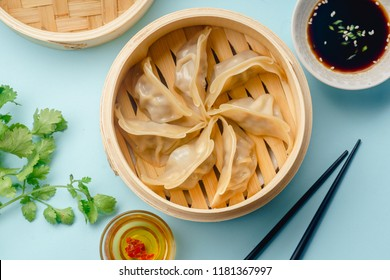 Gyoza dumplings with duck cooked in bamboo steamer on blue background served with soy sauce and cilantro. Top view, flat lay