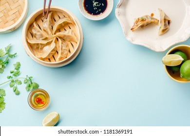 Gyoza dumplings with duck cooked in bamboo steamer on blue background served with soy sauce and cilantro. Top view, flat lay with copy space
