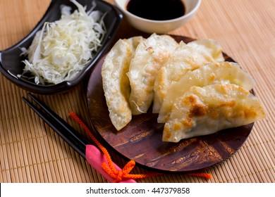 Gyoza dumplings on mini wooden dish, popular japanese food