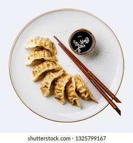 Gyoza dumplings on plate, chopsticks and soy sauce isolate