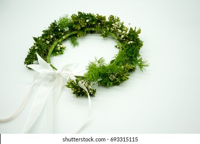 Gypso and green leaves crown with long white ribbon for flower girl at wedding ceremony isolated on white background.