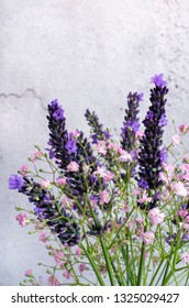 Gypsophilia and Lavender against a cracked plaster effect background.
