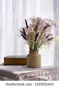 Gypsophilia & Lavender with an old book by a bright window.