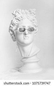 Gypsum statue of Apollo's head. Man. Statue. Plaster statue of Apollo's head in earphones and white sunglasses.