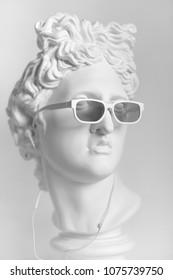 Gypsum statue of Apollo's head. Man. Statue. Plaster statue of Apollo's head in earphones and white sunglasses.