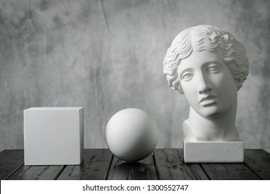 Gypsum white cube, sphere and head of an antique woman simple geometric shape on a gray fabric art background for learning to draw. Drapery and folds.