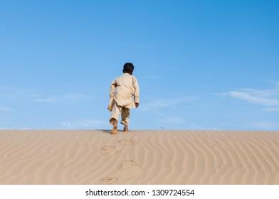 Gypsy boy hiking in the Thar desert