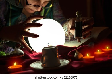 Gypsy fortune teller holding bottle with potion in her hand with another hand around crystal ball