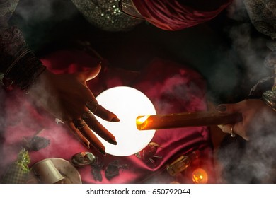 Gypsy fortune teller woman holding candle above crystal ball