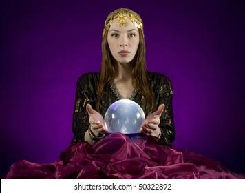 Gypsy fortune-teller,  gazes into crystalball.