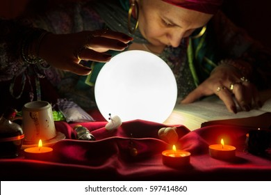 Gypsy fortuneteller reading spells from cursed book and using witchcraft
