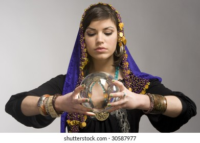 Gypsy fortuneteller uses a crystal ball to foretell the future
