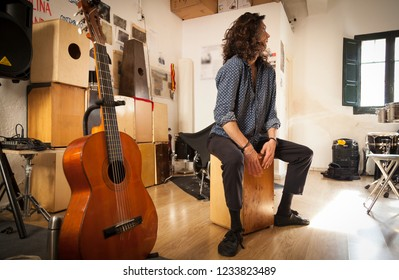 Gypsy styled percussionist smiling portrait enjoying while playing udu on a music studio with speakers, drums, flamenco drum box and spanish guitar on the background with blurry images on the wall.