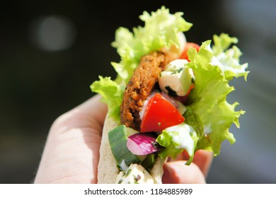 A gyro made from insect burger patties, inside pita bread and on a wooden tray. Insect burgers made from mealworm protein tend to have a taste similar to falafel.