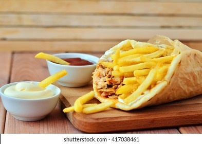 Gyro on a wooden table. Gyro, fries and two sauces on wooden background