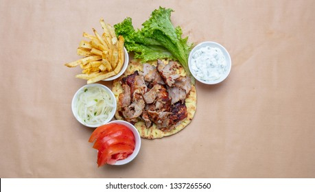 Gyro pita ingredients. Shawarma, gyros, pita bread, vegetables and tzatziki sauce, top view, copy space. Traditional turkish, greek meat food.