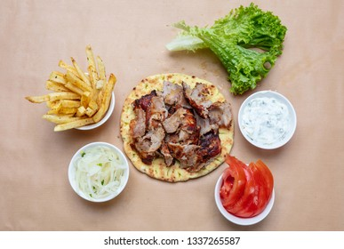 Gyro pita ingredients. Shawarma, gyros, pita bread, vegetables and tzatziki sauce, top view. Traditional turkish, greek meat food.