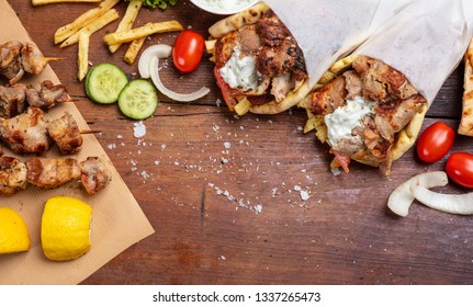 Gyro pita, shawarma, souvlaki. Traditional turkish, greek food. Two pita bread wraps and meat skewers on wooden table, copy space, top view