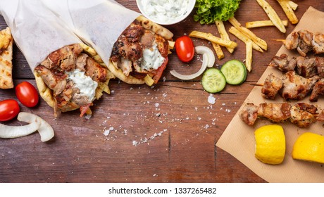 Gyro pita, shawarma, souvlaki. Traditional turkish, greek meat food. Two pita bread wraps and meat skewers on wooden table, copy space, top view