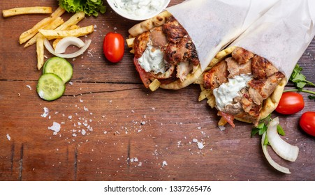 Gyro pita, shawarma, take away, street food. Two pita bread wraps with meat, traditional greek turkish food on wooden table, copy space