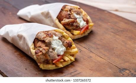 Gyro pita, shawarma, take away, street food. Two pita bread wraps with meat, traditional greek turkish food on wooden table, copy space