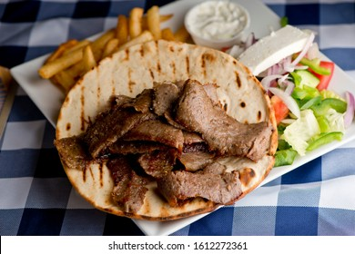 Gyro. Thin slices of seasoned beef, cut off a spit. Served in warm pita bread with bell peppers, heirloom tomatoes, red onions and topped with tzatziki, a dip made w/ Greek yogurt cucumbers lemons