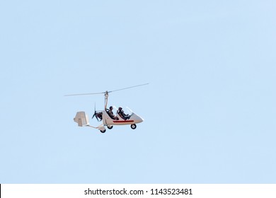 Gyrocopter or autogyro in flight in the blue sky