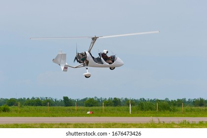 The gyroplane passes over the runway.