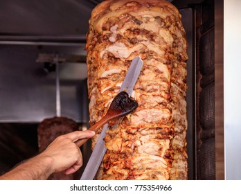 Gyros or doner, Middle East traditional food. Man's hands holding a knife, cutting slices from a vertical skewer