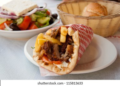 Gyros Pita, mediterranean street food and greek salad. Gyros, classic Greek pita sandwiches, are a favourite street food in Greece and are the Greek version of fast food