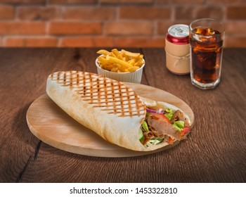 Gyros pita sandwich with french fries and cola on wooden background. For fast food restaurant design or fast food menu