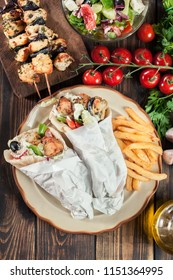 Gyros souvlaki wrapped in a pita bread with french fries. Greek dish. Top view