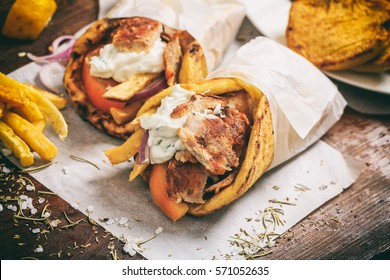 Gyros souvlaki wrapped in a pita bread on a wooden background