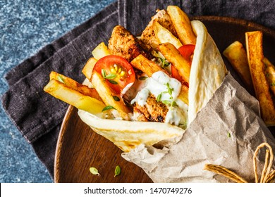 Gyros souvlaki wraps in pita bread with chicken, potatoes and tzatziki sauce, blue background, top view.