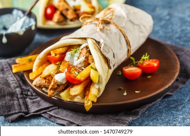 Gyros souvlaki wraps in pita bread with chicken, potatoes and tzatziki sauce, blue background.