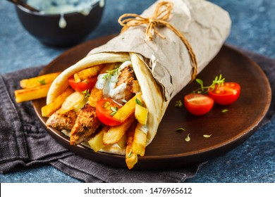 Gyros souvlaki wraps in pita bread with chicken, potatoes and tzatziki sauce, blue background.
