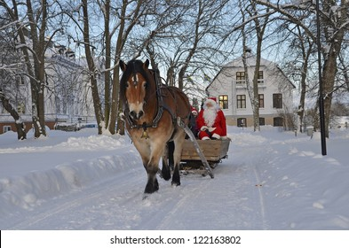 GYSINGE, SWEDEN - DECEMBER 09: Unidentified Santa Claus goes to the traditional Christmas market in the sled with brown horse at Christmas time in Gysinge on December 09, 2012 in Gysinge Sweden