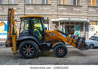 Gyumri, Armenia - October 12, 2018: Yellow JCB excavator with decorated wheels during work on Gorki Street