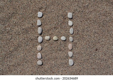 H letter made of stones on sand